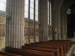 Wooden pews and stone columns inside St Michael's Abbey